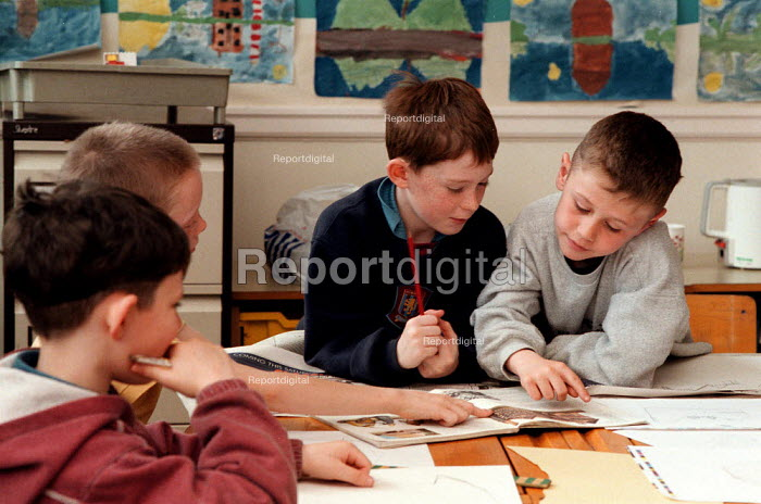 Pupils helping each other learn and drawing facades of buildings from history book, lesson at a Combined Junior and Infant school in the Midlands - John Harris - 1996-05-20