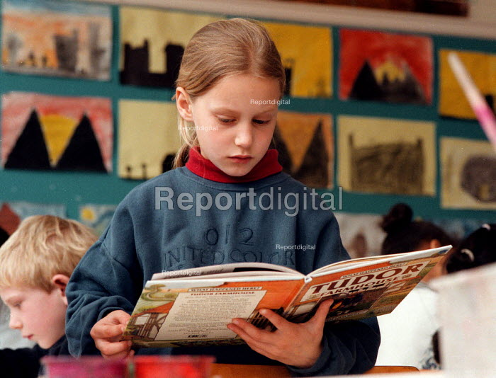 Pupil reading book of buildings from history, lesson at a Combined Junior and Infant school in the Midlands - John Harris - 1996-06-20