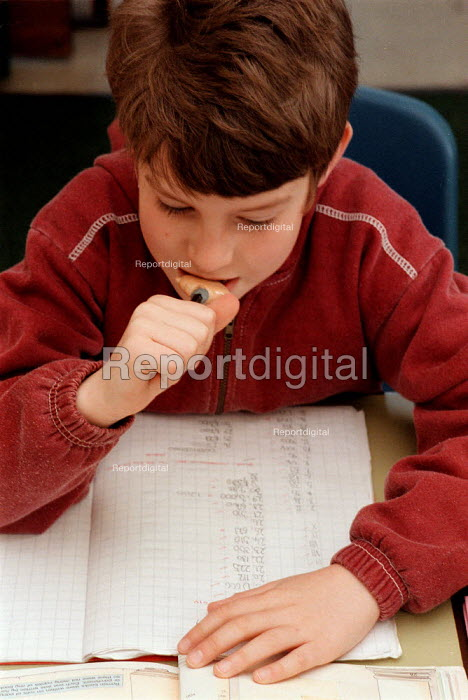 Pupil reading maths marked at a Combined Junior and Infant school in the Midlands - John Harris - 1996-05-20