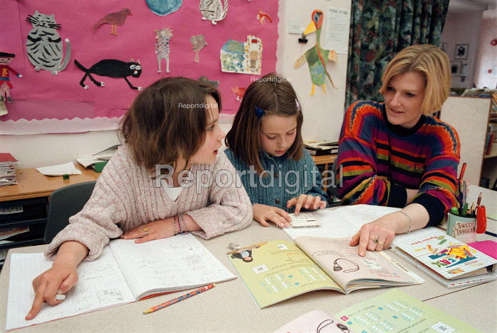 Teacher helping pupils using a calculator and text book, investigating maths at a Combined Junior and Infant school in the Midlands - John Harris - 1996-05-20