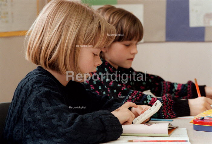 Pupils using a calculator, investigating maths at a Combined Junior and Infant school in the Midlands - John Harris - 1996-05-20