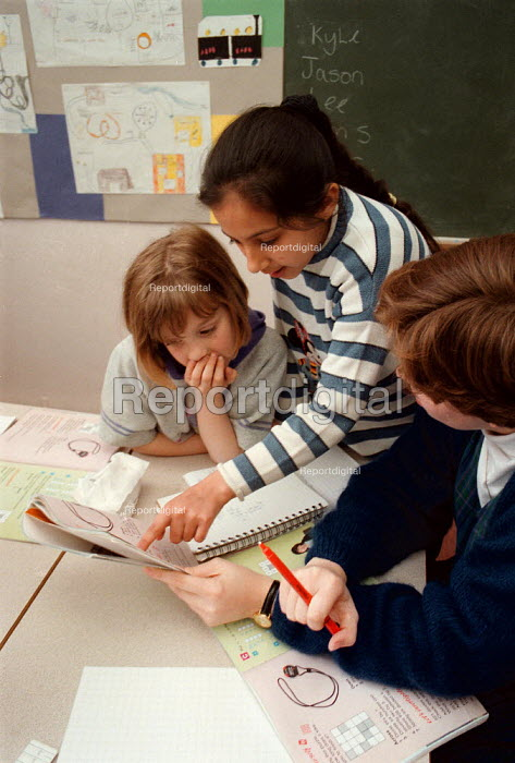 Teacher helping pupils investigating maths at a Combined Junior and Infant school in the Midlands - John Harris - 1996-05-20
