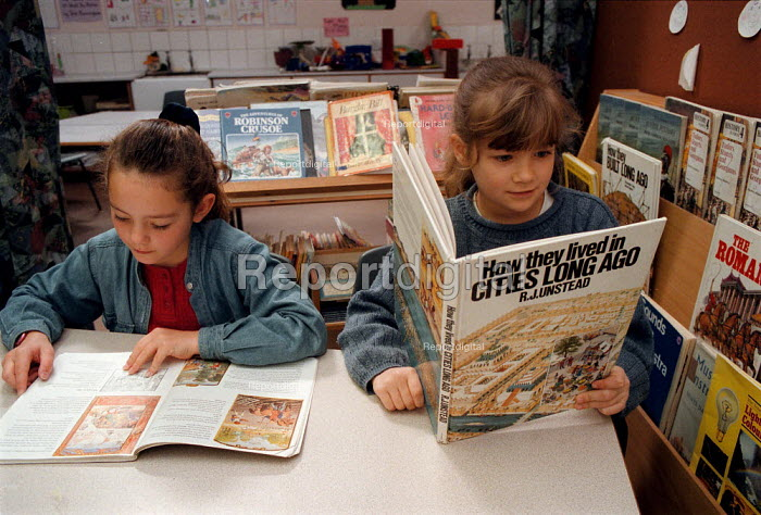 Pupils sitting quietly reading illustrated history books in the library area of a classroom at a Combined Junior and Infant school in the Midlands - John Harris - 1996-05-20
