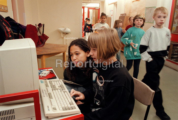 Pupils helping each other to use a computer at a Combined Junior and Infant school. - John Harris - 1996-05-20