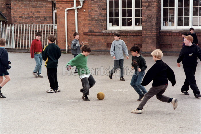 Boys playing football in the playground at break time, Combined Junior and Infant school. - John Harris - 1996-05-20