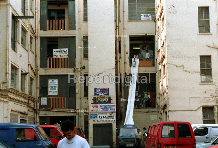 Loading garments into van, sweatshops in old factory Leicester - John Harris - 1996-08-16