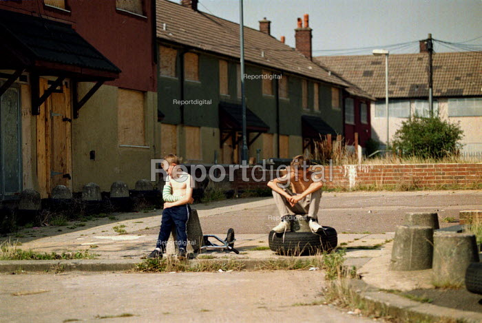 Children on a street of boarded up local authority housing on the Wood End estate Coventry locked boards, concrete bollards, and shutters prevent vandalism in a hard to let area of low incomes, and high unemployment. - John Harris - 1999-09-02