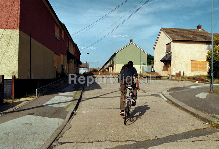 Cyclist on the street of boarded up local authority housing on the Wood End estate Coventry locked boards, concrete bollards, and shutters prevent vandalism in a hard to let area of low incomes, and high unemployment. - John Harris - 1999-09-02