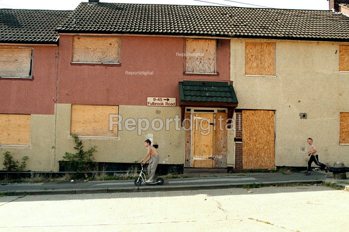 Children playing on a street of boarded up local authority housing on the Wood End estate Coventry locked boards to prevent vandalism in a hard to let area of low incomes, and high unemployment. - John Harris - 1999-09-02