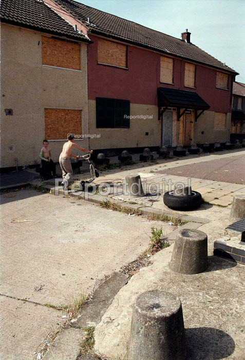 Children playing on a street of boarded up local authority housing on the Wood End estate Coventry locked boards to prevent vandalism, and concrete bollards to stop joyriding in a hard to let area of low incomes, and high unemployment. - John Harris - 1999-09-02