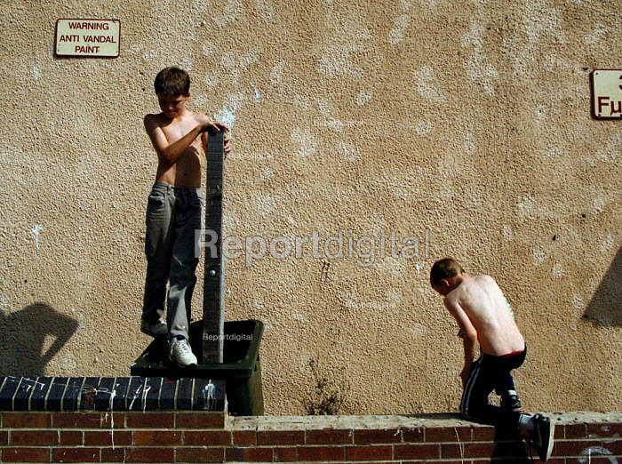 Children playing on a street of boarded up local authority housing on the Wood End estate Coventry locked boards and anti vandal paint to try and prevent vandalism, in a hard to let area of low incomes, and high unemployment. - John Harris - 1999-09-02