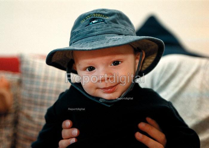 Baby boy at 15 weeks wearing a hat - John Harris - 1999-09-30