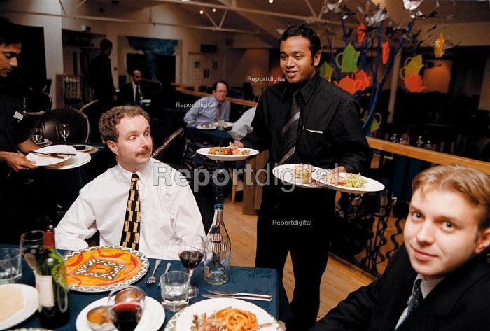 Waiter serving meals to buisness lunch customers at Smimia Pinks Indian Restaurant Birmingham - John Harris - 1999-10-08