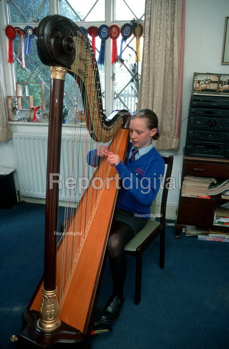 Secondary school pupil practicing playing her harp in the front room at home. - John Harris - 1999-07-17