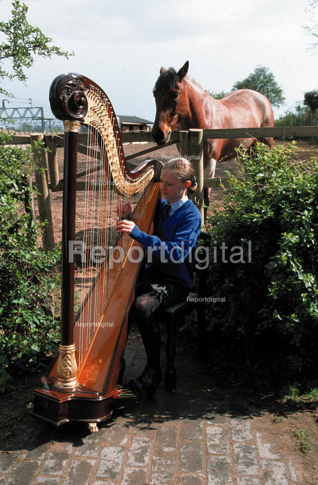 Secondary school pupil practicing playing her harp in the yard at home, while her pony listens. - John Harris - 1999-07-17