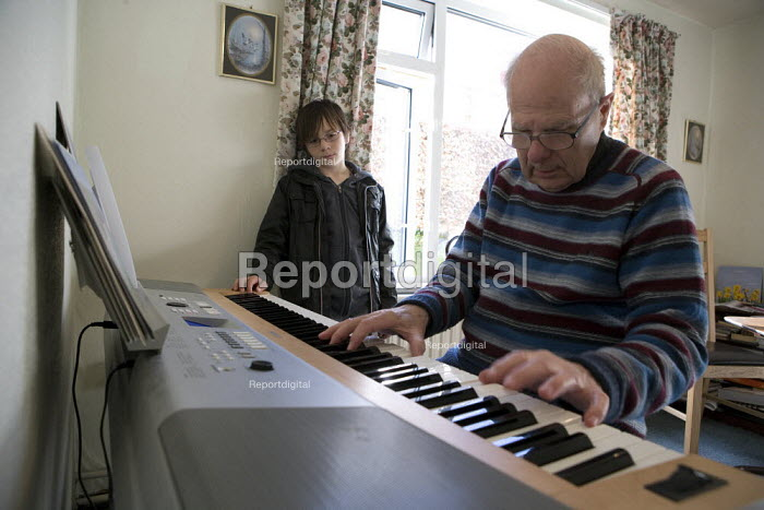 Emilio listening to his grandad play the piano in his sheltered accommodation, Telford. - John Harris - 2010-03-27