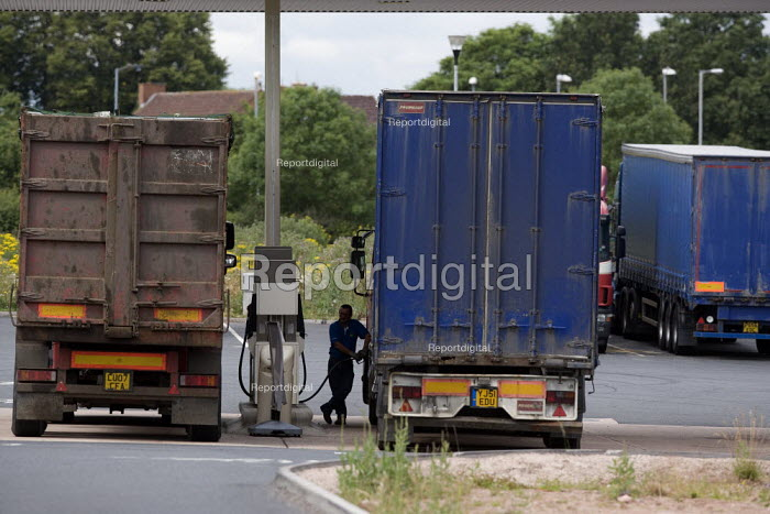 Lorry driver filling up his HGV with diesel fuel from a pump on the forcourt at a service station. - John Harris - 2011-06-30