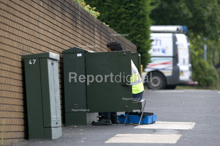 BT engineer working on telephone lines in a junction cabinet box. - John Harris - 2011-07-28