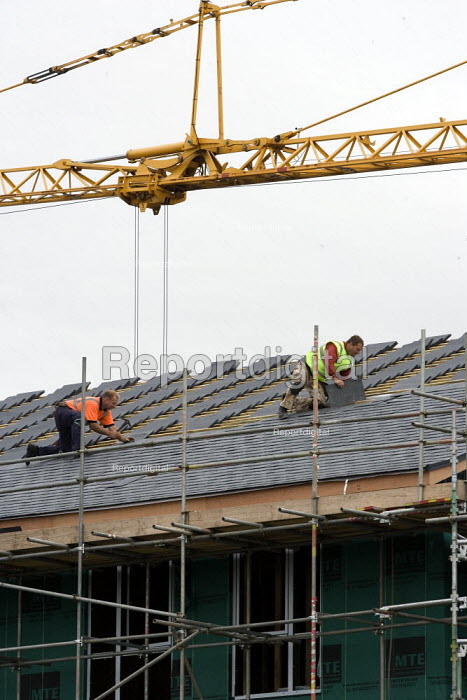Roofers laying tiles on the roof of a construction site. - John Harris - 2011-09-10