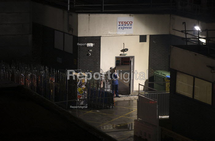 A young shopworker takes a break at the back door of a Tesco express store. Birmingham City centre at night. - John Harris - 2011-11-12