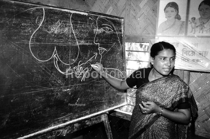 Rural woman health worker teaching hygiene by illustrating the path of infection. Bangladesh. 1998 - Jim Holmes - 1998-07-03