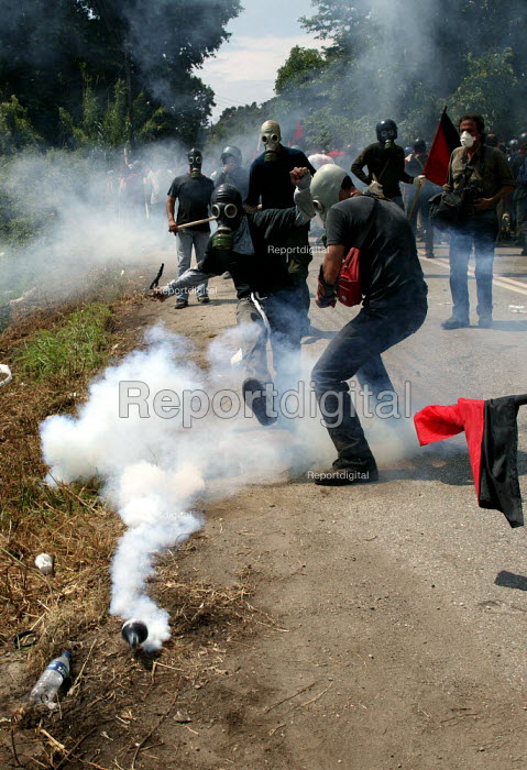 Anarchist kicks back a CS Gas canister towards police lines as riot attack protesters during clashes inside the Red Zone security cordon surrounding the European Union Summit in Halkidiki, Greece. - Jess Hurd - 2003-06-20