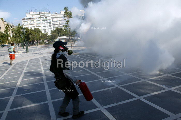 Anarchist protester with fire extinguisher after riot police fired CS Gas into the demonstration. European Union Summit Thessaloniki, Greece. - Jess Hurd - 2003-06-21