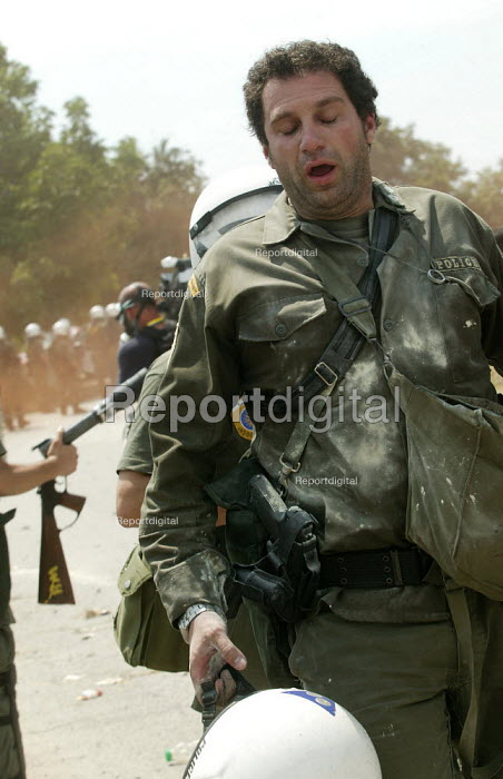 Riot police forced to leave the battle field after suffering respiratory problems due to tear gas saturation during clashes in the Red Zone security cordon surrounding the European Union Summit meeting in Thessaloniki, Greece. - Jess Hurd - 2003-06-20