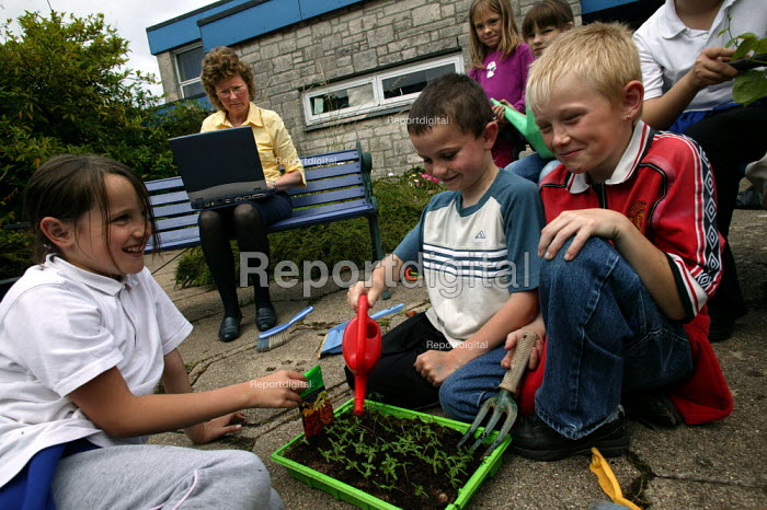 Year 3 children from Langley Junior School take part in gardening activities whilst teacher Pennie Hagan works on her Pathfinder laptop. Part of the Government Pathfinder project, piloted in Plymouth to reduce teacher workload. - Jess Hurd - 2003-07-02