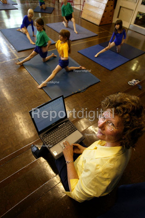 Year 3 children from Langley Junior School take part in gym activities whilst teacher Pennie Hagan works on her Pathfinder laptop. Part of the Government Pathfinder project, piloted in Plymouth to reduce teacher workload. - Jess Hurd - 2003-07-02