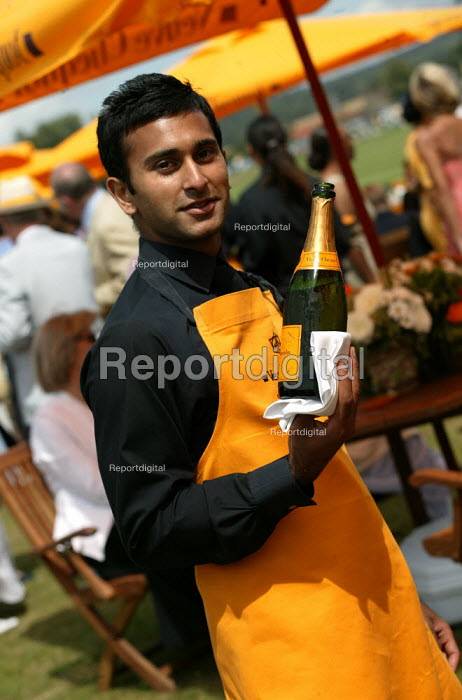 Waiter serves wealthy at The Veuve Clicquot Gold Cup Polo Final, Cowdray Park Polo Club. West Sussex. - Jess Hurd - 2003-07-20
