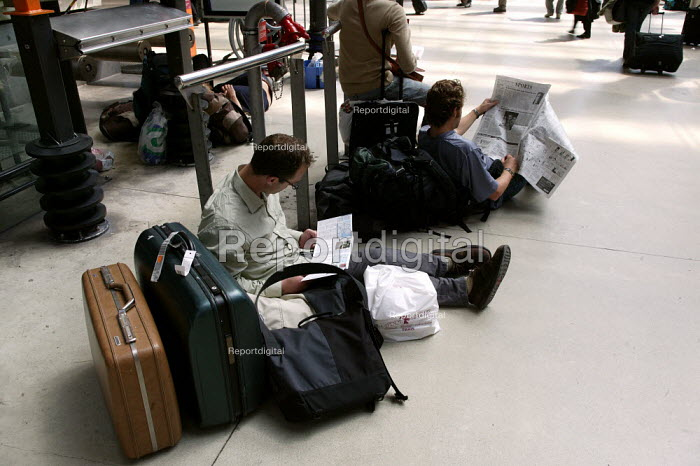 Passengers reading whilst waiting for a train at the Gare du Nord Railway Station, Paris. - Jess Hurd - 2003-07-30