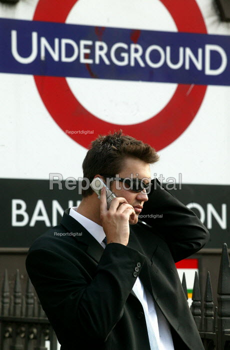 City businessman uses his mobile phone outside Bank Underground station, City of London. - Jess Hurd - 2003-07-15