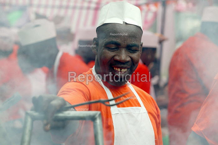 A chef cooks jerk chicken on a stall at the Notting Hill Carnival. London. - Jess Hurd - 2003-08-25