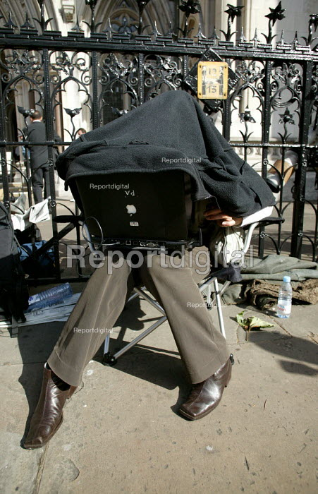 Fiona Hanson PA photographer shielding her laptop from the sun while she prepares to send her photographs from the High Court, London - Jess Hurd - 2003-08-19