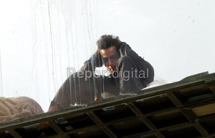 American magician David Blaine sits in a sealed perspex box suspended 40 feet in the air near Tower Bridge in London. He plans a feat of endurance, spending 44 days alone without food. - Jess Hurd - 2003-09-06