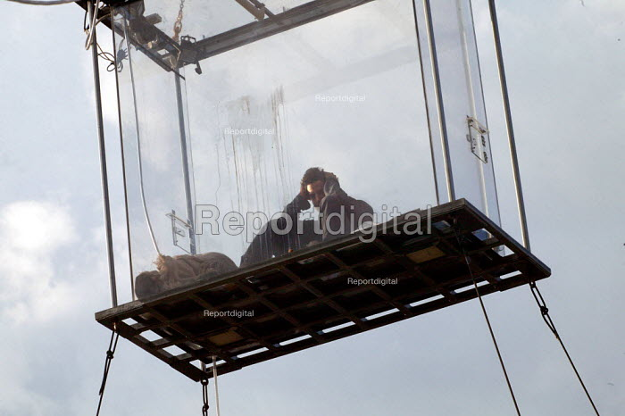 American magician David Blaine sit in a sealed perspex box suspended 40 feet in the air near Tower Bridge in London. He plans a feat of endurance, spending 44 days alone without food. - Jess Hurd - 2003-09-06