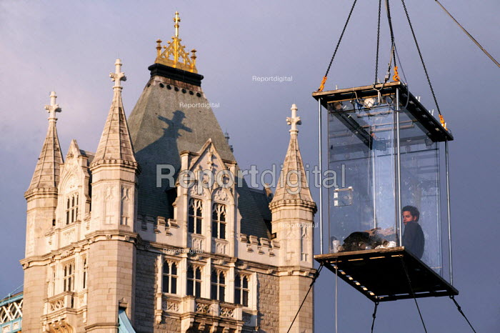American magician David Blaine hangs in a sealed perspex box suspended 40 feet in the air near Tower Bridge in London. He plans a feat of endurance, spending 44 days alone without food. - Jess Hurd - 2003-09-06