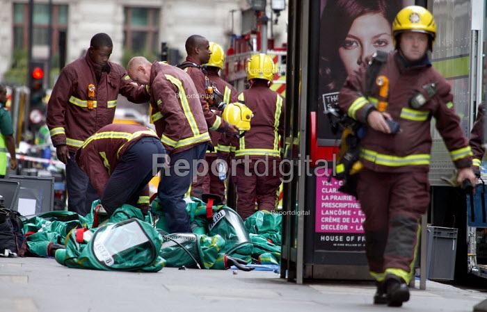 Firefighters remove their chemical protection suits after finishing an exercise simulating a chemical agent terrorist attack on Bank Underground station in London. - Jess Hurd - 2003-09-06