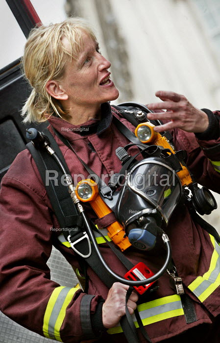 A female firefighter carrying breathing apparatus after finishing an exercise simulating a chemical agent terrorist attack on Bank Underground station in London. - Jess Hurd - 2003-09-06