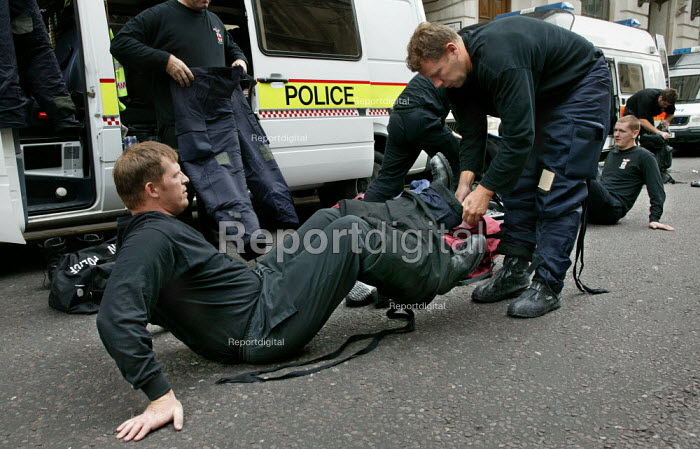 City of London and British Transport Police officers trained in chemical and biological defence remove their protection suits during an exercise simulating a chemical agent terrorist attack on Bank Underground station in London. - Jess Hurd - 2003-09-06