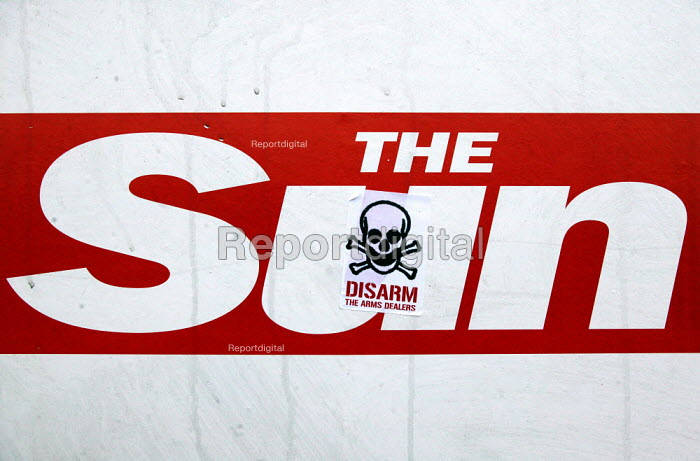 Protesters sticker on an advertisement for The Sun reads Disarm the Arms Fair at Defence Systems and Equipment International Arms Fair, Excel Centre, London. - Jess Hurd - 2003-09-10