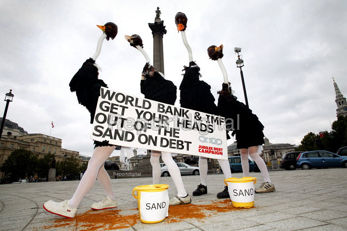Jubilee Debt campaign perform an ostrich protest against third world debt. Urging the World Bank and IMF to take action against poverty and not keep their heads in the sand. Trafalgar Square, London. - Jess Hurd - 2003-09-19