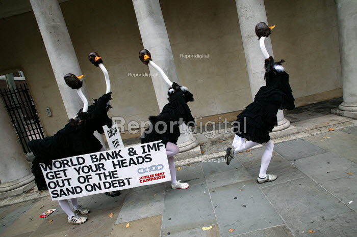 Jubilee Debt campaign perform an ostrich protest against third world debt. Urging the World Bank and IMF to take action against poverty and not keep their heads in the sand. London. - Jess Hurd - 2003-09-19