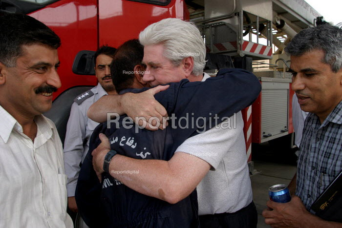 FBU member Brian Joyce greets Iraqi firefighter in the Civic Defense Department. On the first solidarity trip, UK trade union members meet with representatives from the Workers Democratic Trade Union Movement WDTUM. Baghdad, Iraq. - Jess Hurd - 2003-10-06