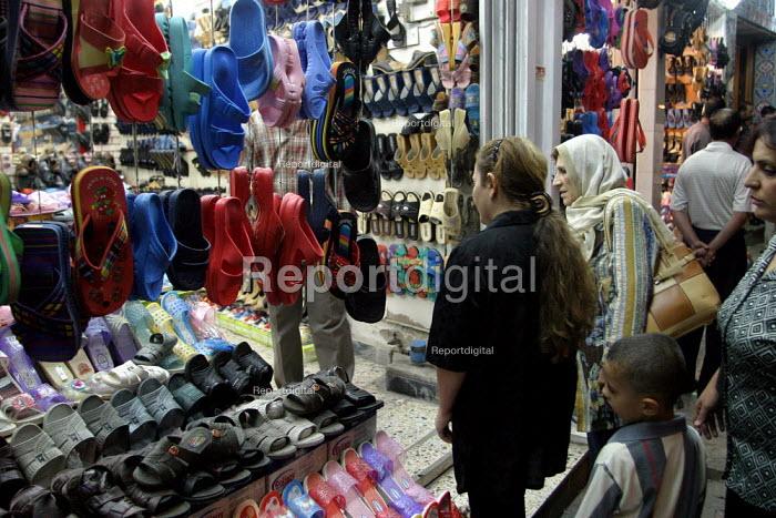 Iraqis shop for flip flops before curfew. Baghdad, Iraq. - Jess Hurd - 2003-10-07