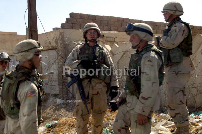 US Army soldiers stand around smoking cigarettes outside one of their bunkered bases. Baghdad, Iraq. - Jess Hurd - 2003-10-07