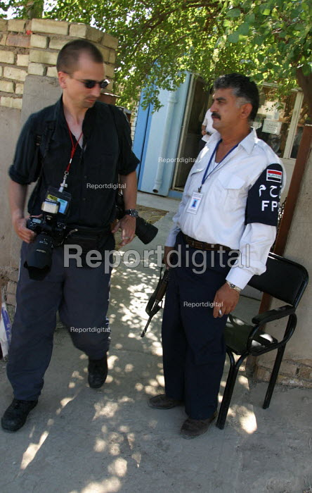 Guy Smallman NUJ walks past an Iraqi policeman with an AK 47 outside the Ministry for Labour. UK trade union members meet with representatives from the Workers Democratic Trade Union Movement WDTUM. Baghdad, Iraq. - Jess Hurd - 2003-10-05