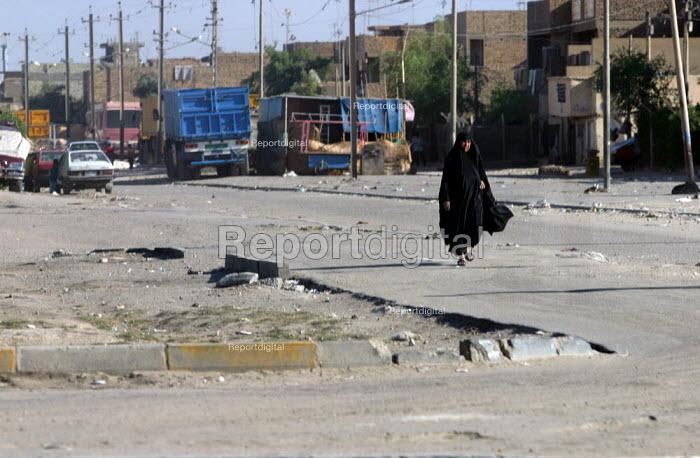 Iraqi woman walks the streets of Sadr City, Baghdad, Iraq. - Jess Hurd - 2003-10-05