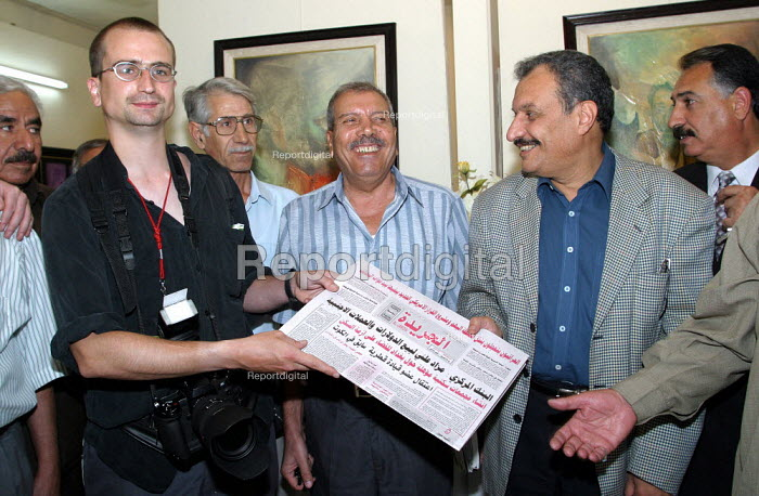 Guy Smallman NUJ accepts the newspaper of the Arab Socialist League who can publish openly but still with threats of repression and censorship under occupation. UK trade union members meet with representatives from the Workers Democratic Trade Union Movement WDTUM. Baghdad, Iraq. - Jess Hurd - 2003-10-05